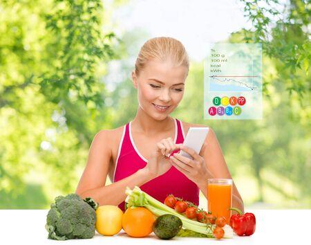 donna con verdure che punta allo smartphone Archivio Fotografico