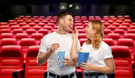 happy couple in t-shirts eating popcorn at cinema