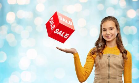 glückliches Teenager-Mädchen, das Verkaufsschild zeigt