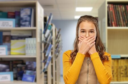 scared student girl closing mouth at library