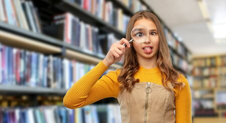 teenage girl with magnifying glass at library 스톡 콘텐츠