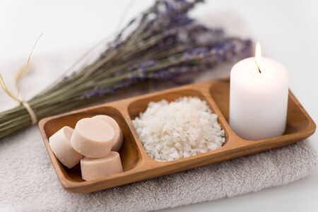 beauty and wellness concept - sea salt, soap and candle on wooden tray and bunch of lavender on bath towel Imagens