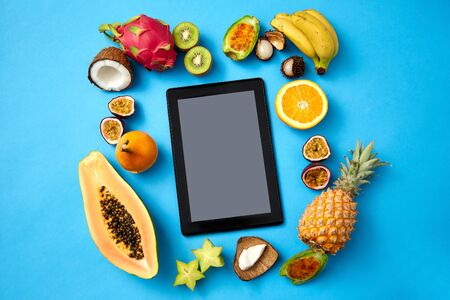 food, diet and healthy eating concept - different exotic fruits around tablet pc computer on blue background Stock Photo