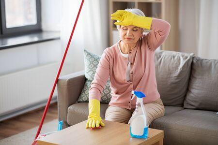 müde ältere Frau, die zu Hause den Tisch putzt Standard-Bild