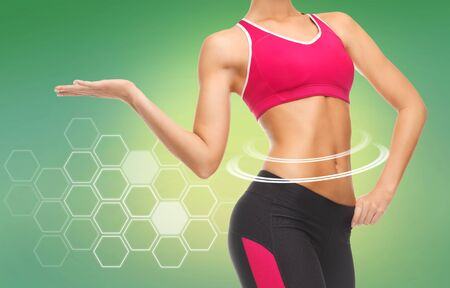 sport, fitness and diet concept - close up of slim fit womans body with trained abs over green background