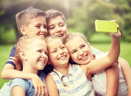 enfants ou amis heureux prenant un selfie dans un parc d'été