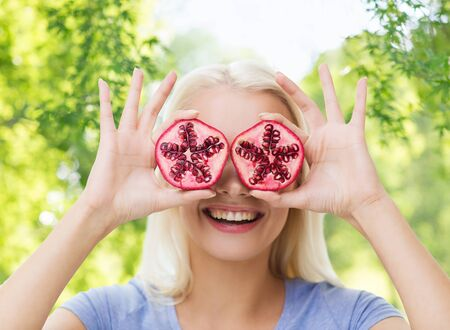 healthy eating, food, diet and people concept - happy smiling woman having fun and covering her eyes with pomegranate over green natural background