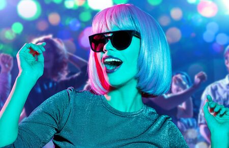 nightlife, entertainment and people concept - happy young woman wearing pink wig and black sunglasses dancing at nightclub over lights background