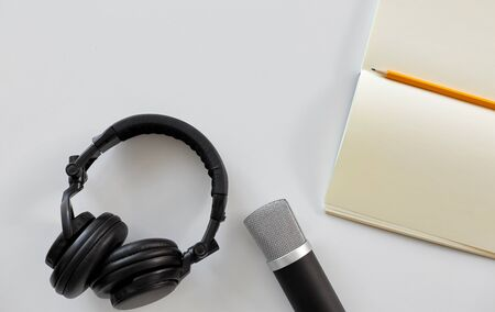technology, sound recording and podcast concept - headphones , microphone and notebook with pencil on white background