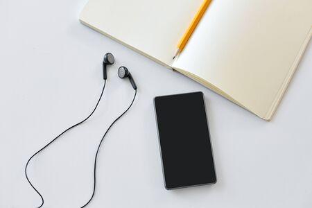 earphones, smartphone and notebook with pencil Banco de Imagens