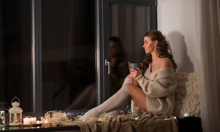 woman with coffee or tea cup on windowsill at home Banco de Imagens