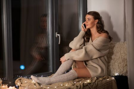 woman sitting on sill and calling on smartphone Banco de Imagens