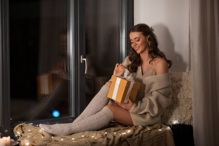 woman with christmas gift at home at night