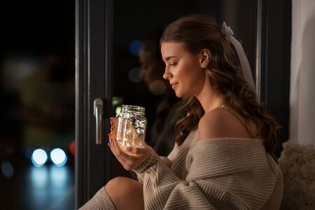woman with garland lights in glass mug at home