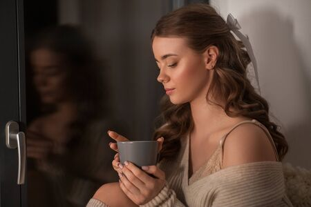 woman with coffee or tea cup at window at home
