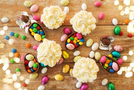 cupcakes with chocolate eggs and candies on table Standard-Bild