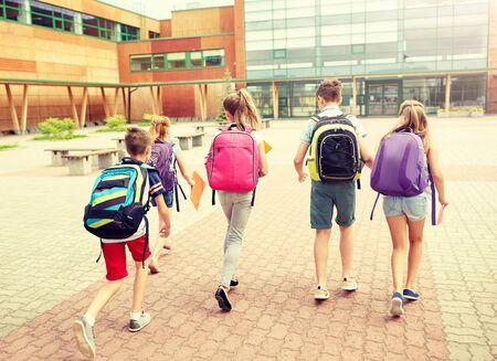 Grundschulbildung, Freundschaft, Kindheit und Menschenkonzept - Gruppe glücklicher Grundschüler mit Rucksäcken, die im Freien laufen