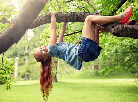 friendship, childhood, leisure and people concept - happy smiling little redhead girl hanging upside down on tree in summer park Stock Photo