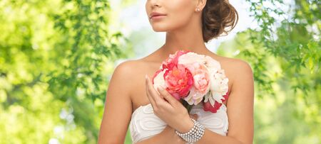young woman or bride with bouquet of flowers