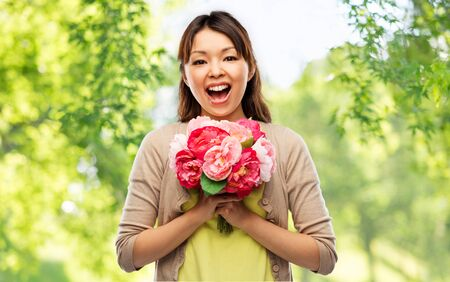 happy laughing asian woman with bunch of flowers