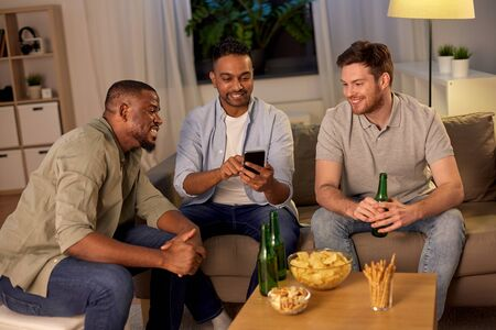 male friends with smartphone drinking beer at home