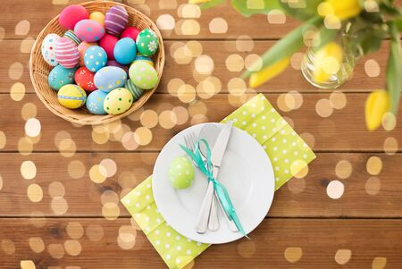 easter eggs in basket, plates, cutlery and flowers
