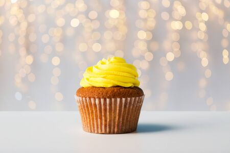 food, junk-food, culinary, baking and eating concept - close up of cupcake or muffin with yellow buttercream frosting over festive lights on background