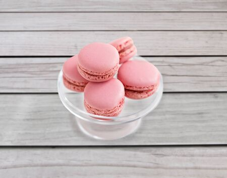 sweets, pastry and food concept - pink macaroons on glass confectionery stand over grey boards on background