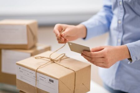 delivery, mail service, people and shipment concept - close up of woman packing parcel box and tying tag by rope at post office