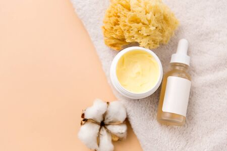 beauty, spa and wellness concept - close up of body butter, natural sponge and essential oil on bath towel Stock Photo