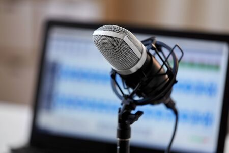 technology and audio equipment concept - close up of microphone at recording studio or radio station