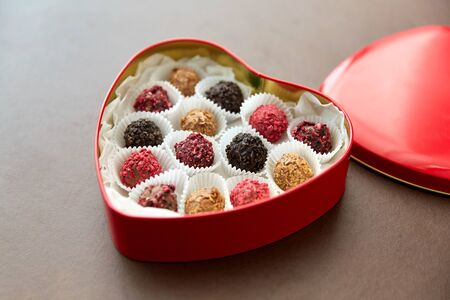 sweets, confectionery and food concept - candies in red heart shaped chocolate box on brown background