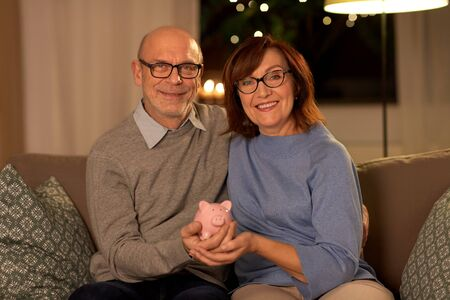 happy senior couple with piggy bank at home