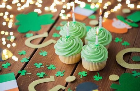 st patricks day, holidays and celebration concept - green cupcakes with candles, horseshoes and shamrock on wooden table over festive lights