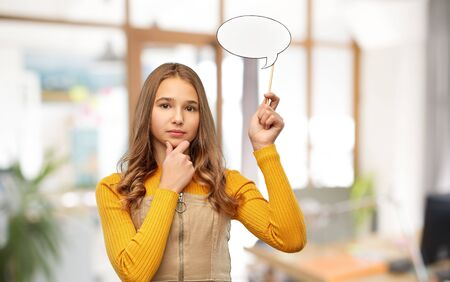 teenage girl holding speech bubble over office