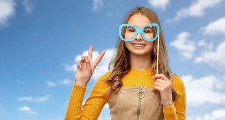 smiling teenage girl with big glasses over sky