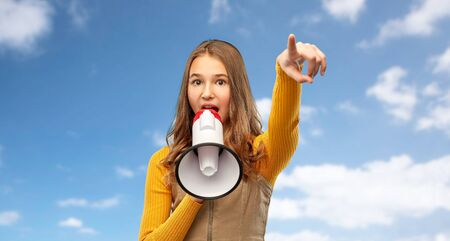teenage girl speaking to megaphone over sky