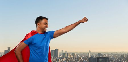 super power and people concept - indian man in red superhero cape making winning gesture over tokyo city background 版權商用圖片