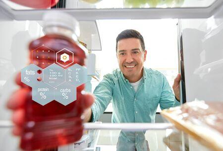 man taking juice from fridge at home kitchen 写真素材