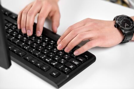 technology and people concept - male hands with red manicure typing on computer keyboard on table