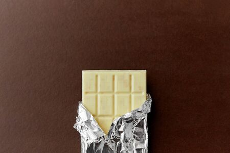 sweets, confectionery and food concept - white chocolate bar in foil wrapper on brown background