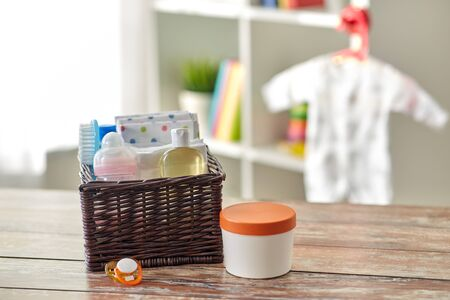 baby things in basket on wooden table at home