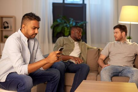 man with smartphone and friends at home at night
