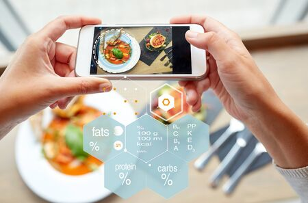 food, eating, technology, culinary and people concept - close up of hands with gazpacho soup on smartphone screen and nutritional value chart at restaurant