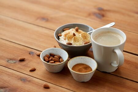 food and breakfast concept - oatmeal porridge in bowl with sliced banana, almond nuts and cinnamon and cup of coffee on wooden table