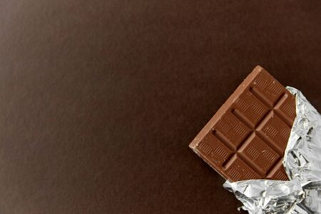 sweets, confectionery and food concept - milk chocolate bar in foil wrapper on brown background