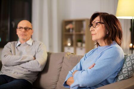 unhappy senior couple sitting on sofa at home Stock Photo
