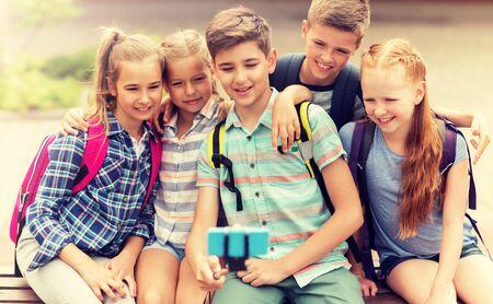 happy elementary school students taking selfie