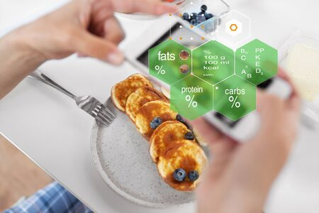 food , eating and technology concept - hands with pancakes and smartphone over nutritional value chart