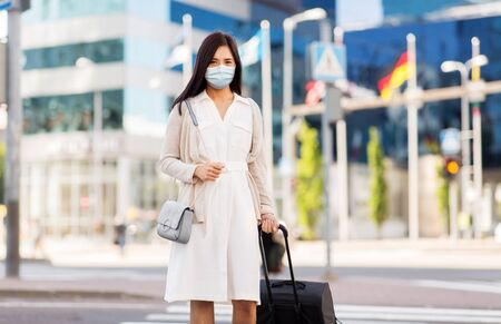 asian woman with travel bag in protective mask Stock Photo